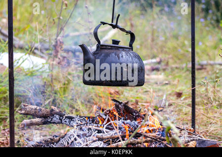 Old kettle over camp fire - Stock Photo