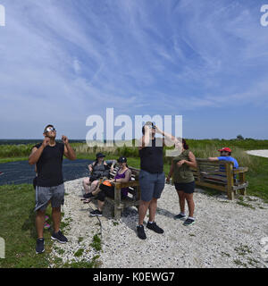 South Merrick, New York, USA. 21st Aug, 2017. Using solar glasses they borrowed, two young men frm Plainview, NY, - Stock Photo