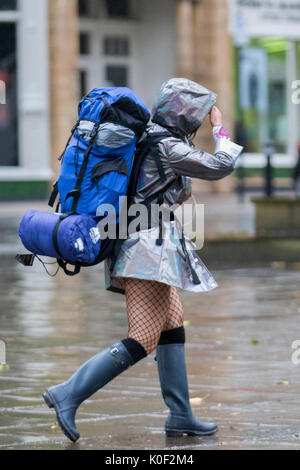 Woman with heavy haversack, wearing a short skirt and net stockings walking in the rain in Preston, Lancashire. - Stock Photo