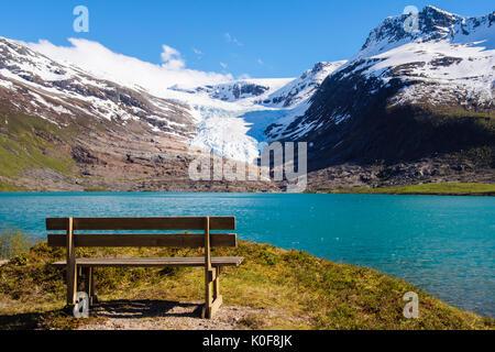 Lakeside empty bench overlooking Svartisvatnet lake to Engabreen or Enga glacier arm of Svartisen ice cap. Saltfjellet - Stock Photo