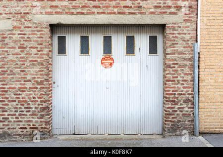 Old white garage door with sign saying no parking in french in Saint-omer, North eastern France - Stock Photo