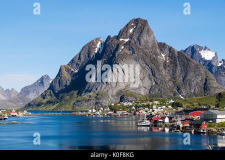 View across the natural fishing harbour to towering mountains above Reine, Moskenes, Moskenesøya Island, Lofoten - Stock Photo