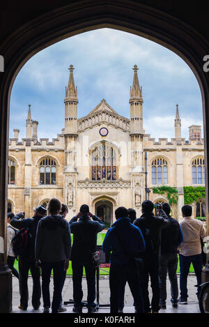 Cambridge university tourists, a group of tourists stand under the arched entrance of Corpus Christi College to - Stock Photo