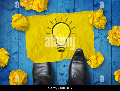 Winning Idea. A businessman looking down at rubbish ideas and turning one into a good idea. - Stock Photo