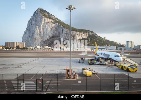 An aircraft on the tarmac at Gibraltar International Airport with Gibraltar Rock seen in the background. - Stock Photo