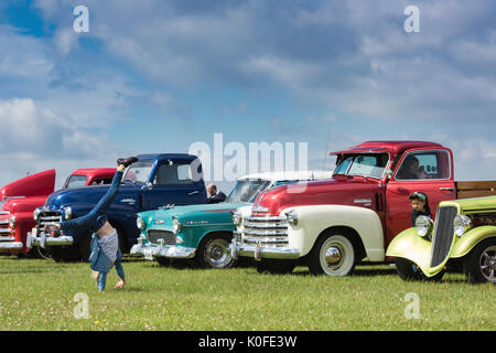 Young girl doing a handstand / cartwheel in front of 1950s Chevrolet pick up trucks at an american car show. Essex. - Stock Photo