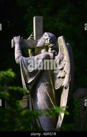an angel holding cross in Highgate cemetery London - Stock Photo