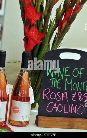 Two bottles of locally produced wine at a farmers market with a sign stating that this is the wine of the month next to some red flowers in a vase.