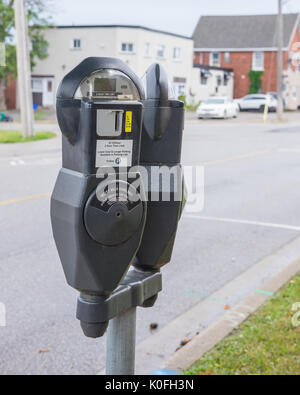 Old style coin operated parking meters on a downtown street. - Stock Photo