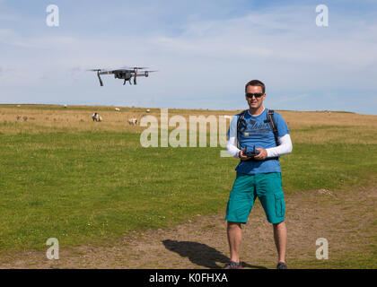 Man flying small drone - Stock Photo