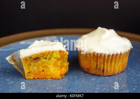 Zucchini and carrot cupcakes with Philadelphia cheese cream on blue plate on black surface - Stock Photo