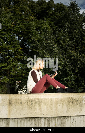 Woman portrait in summer. Girl is sitting outside an office and holding a tablet. Female   in a white furry jacket, - Stock Photo