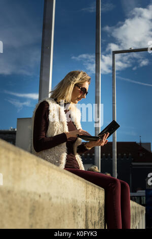 Woman portrait, summer. Blonde girl is sitting outside an office, holding a tablet. Female in a white furry jacket, - Stock Photo