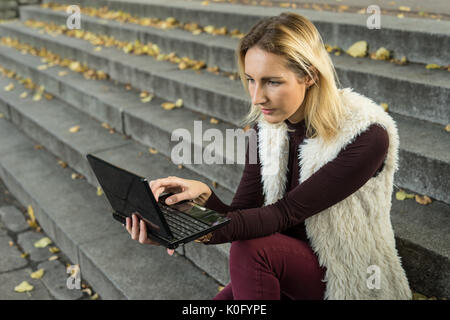 Beautiful young woman portrait. Blond girl is sitting on steps outside an office and holding a tablet. Businesswoman - Stock Photo