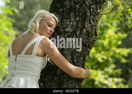 Blonde woman hugging a tree in park. Young girl resting in nature, leaned against a tree - Stock Photo