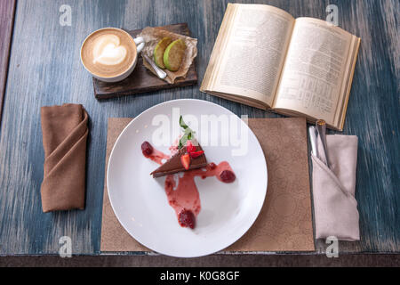 piece of cake with strawberries on a plate with a Cup of coffee on wooden table near old books - Stock Photo