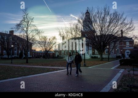 Two students walk on a brick path in front of Gilman Hall on the Keyser Quadrangle of the Homewood campus of the - Stock Photo