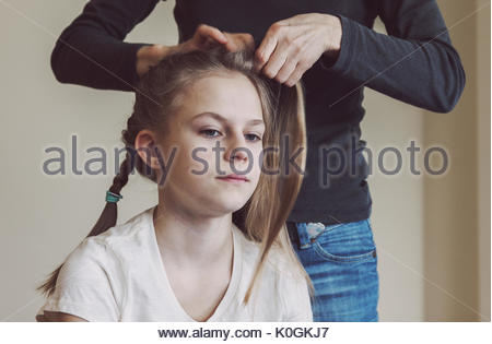 Mother braiding young girls hair. Real life portrait picture of caucasian teen girl with deliberate warm mate filter - Stock Photo