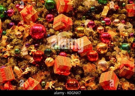 Christmas holiday decorations with glass bulbs, presents, ornaments and tinsel on Christmas tree at Winter WonderFest - Stock Photo