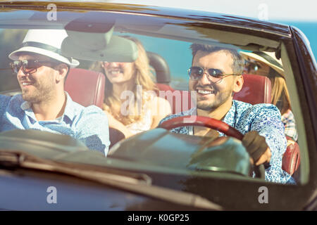 Group of cheerful young friends driving car and smiling in summer - Stock Photo