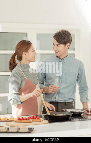 Young smiling couple preparing for a party in kitchen - Stock Photo