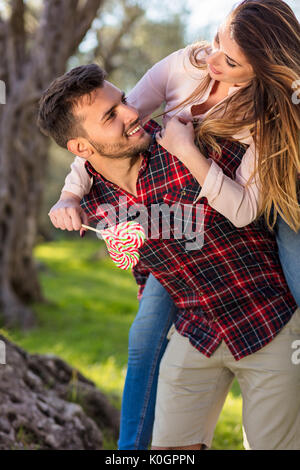 Portrait of smiling handsome man giving piggy back to his girlfriend in the nature - Stock Photo