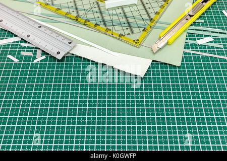 various paper sheets with metal ruler and utility knife on green cutting mat - Stock Photo