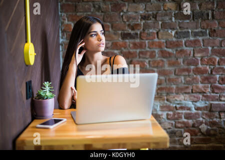 Beautiful Caucasian woman dreaming about something while sitting with portable net-book in modern cafe bar, young - Stock Photo