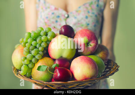 A large wooden plate with ripe fruits in the hands of a young woman. Harvest concept - Stock Photo