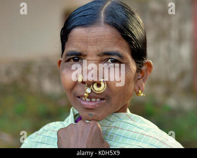 Elderly Indian Adivasi market woman with precious golden nose studs/rings/jewellery and tribal earrings. - Stock Photo