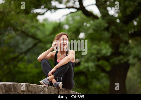Young smiling girl in sportswear listening to music in headphones and looking away in park. Fitness woman. Fitness - Stock Photo