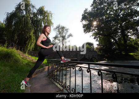 Side view of determined sportswoman looking forward while warming up in sunlight. Fitness woman. Fitness woman in - Stock Photo