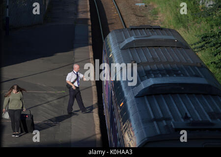 The conductor of the 1821 Colne - Blackpool South Northern Rail train checks the time while waiting departure from - Stock Photo