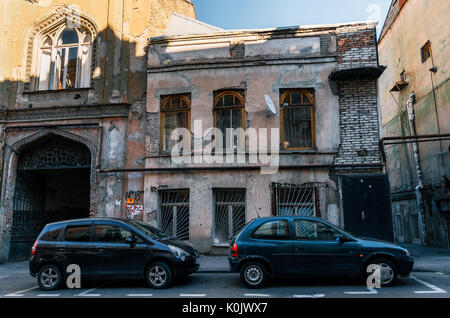 Tbilisi, Georgia - October 15, 2016: Ramshackle old architecture in Tbilisi centre on the background of parked cars - Stock Photo