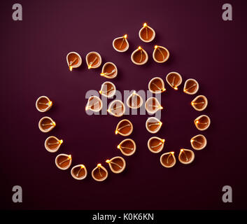 Traditional clay diya lamps arranged in shape of Hindu symbol Om during Diwali celebration - Stock Photo