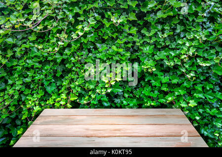 Old wooden vintage table on the background of natural wall from green ivy leaves - Stock Photo
