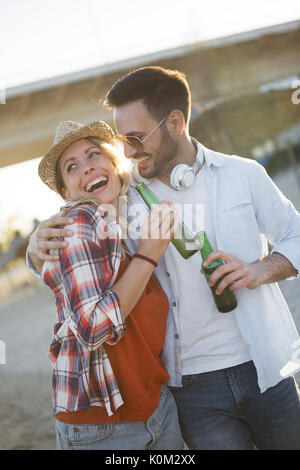 Happy couple smiling and drinking beer at beach - Stock Photo