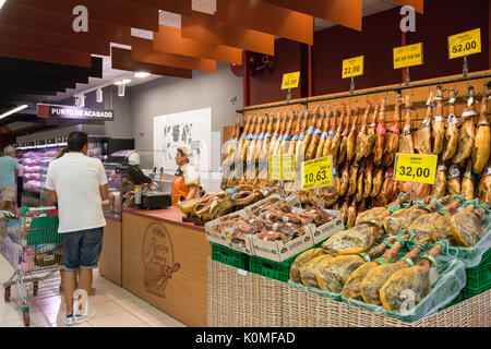 jamon - dry cured ham legs - at typical Spanish supermarket - Stock Photo