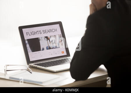 Businessman searching cheap low cost business flight on laptop,  - Stock Photo