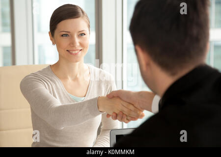 Smiling beautiful woman shaking male hand, arriving at job inter - Stock Photo