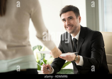 Female job applicant gives resume to recruiter at job interview - Stock Photo