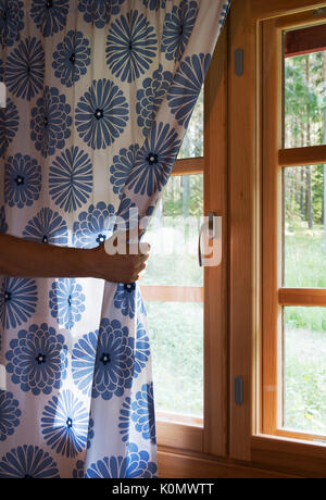 Hand opens curtain on the wooden cottage house window. Bright sunlight shines through. Beautiful summer morning - Stock Photo