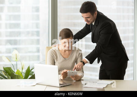 Smiling managers working on tablet, agents using real estate app - Stock Photo