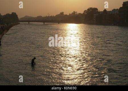 Man taking bath in the Ganga river in Haridwar - Stock Photo
