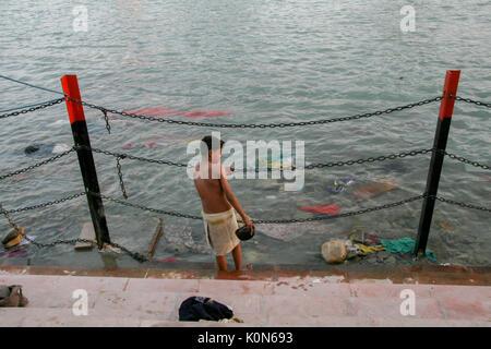 Young boy taking a holy bath in Haridwar - Stock Photo