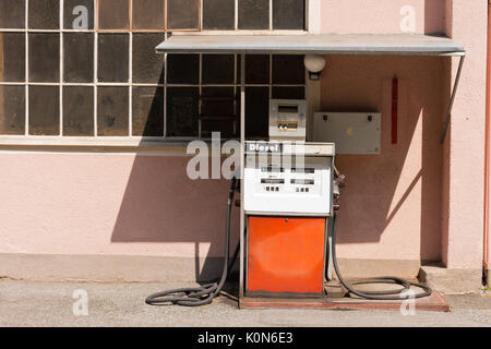 Old diesel petrol pump in Austria. Filling station in front of pink colored house. Warnings in German for safe refueling: - Stock Photo