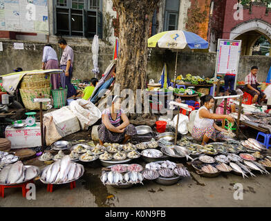 Yangon, Myanmar - Feb 13, 2017. People selling fresh fish at street market in Yangon, Myanmar. Yangon is the country - Stock Photo