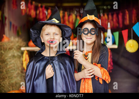 Witch and wizard in scary masks on - Stock Photo
