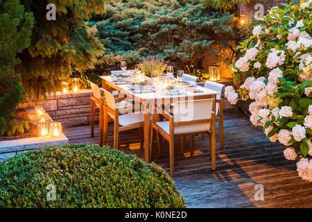 Deutschland, Garten, Terrasse, Holzdeck, Gartenmöbel, moderne Sitzgruppe, gedeckter Tisch, festlich, Tischdeko Lavendel, - Stock Photo