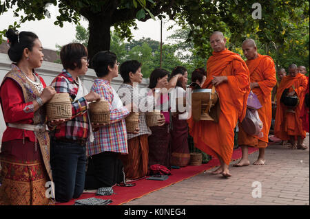 The saffron-clad monks walk along the main street of Luang Prabang, Laos, during alms giving ceremony. With over - Stock Photo